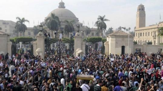 (引用:http://www.timesofisrael.com/pro-morsi-protesters-enter-cairos-tahrir-square/, photo-credit:AP/Mohammed Asad、カイロ大学正門ゲートの様子)